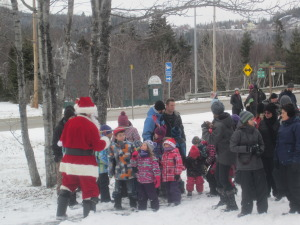 Santa leads the children and their parents to the L'Eauberge
