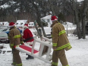 Firs responders and fire personnel carry Santa's throne