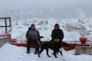 Alan and our friend Don Crockford sitting on top of wharf with ice pack towering over them
